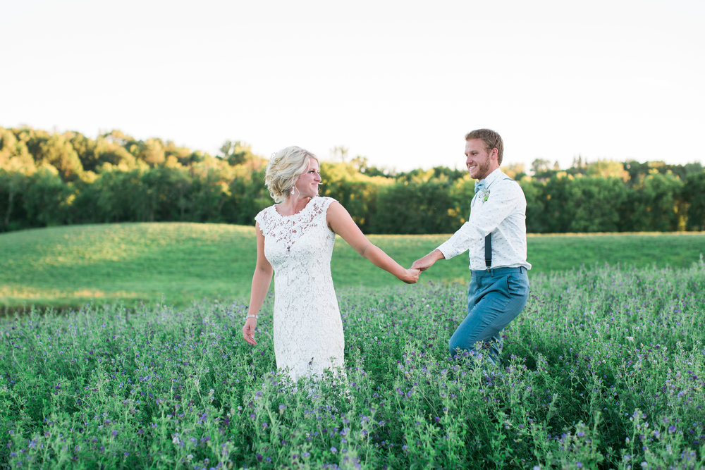 Rural Minnesota wedding with bride and groom walking through a field of flowers