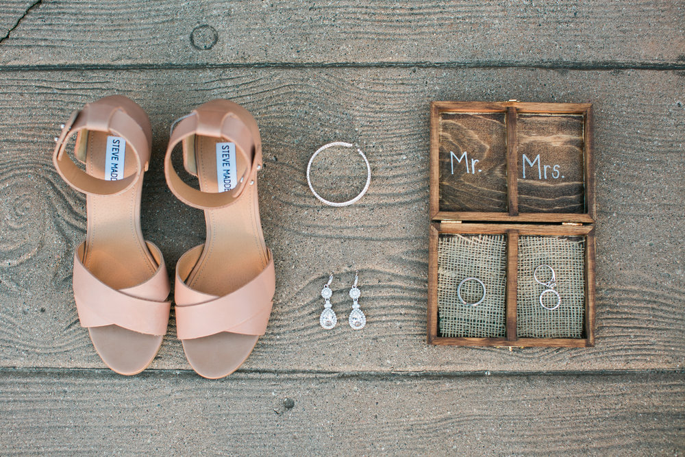 Bridal details of shoes, jewelry, and ring box at rustic summer Minnesota outdoor wedding at The Outpost Center in Chaska