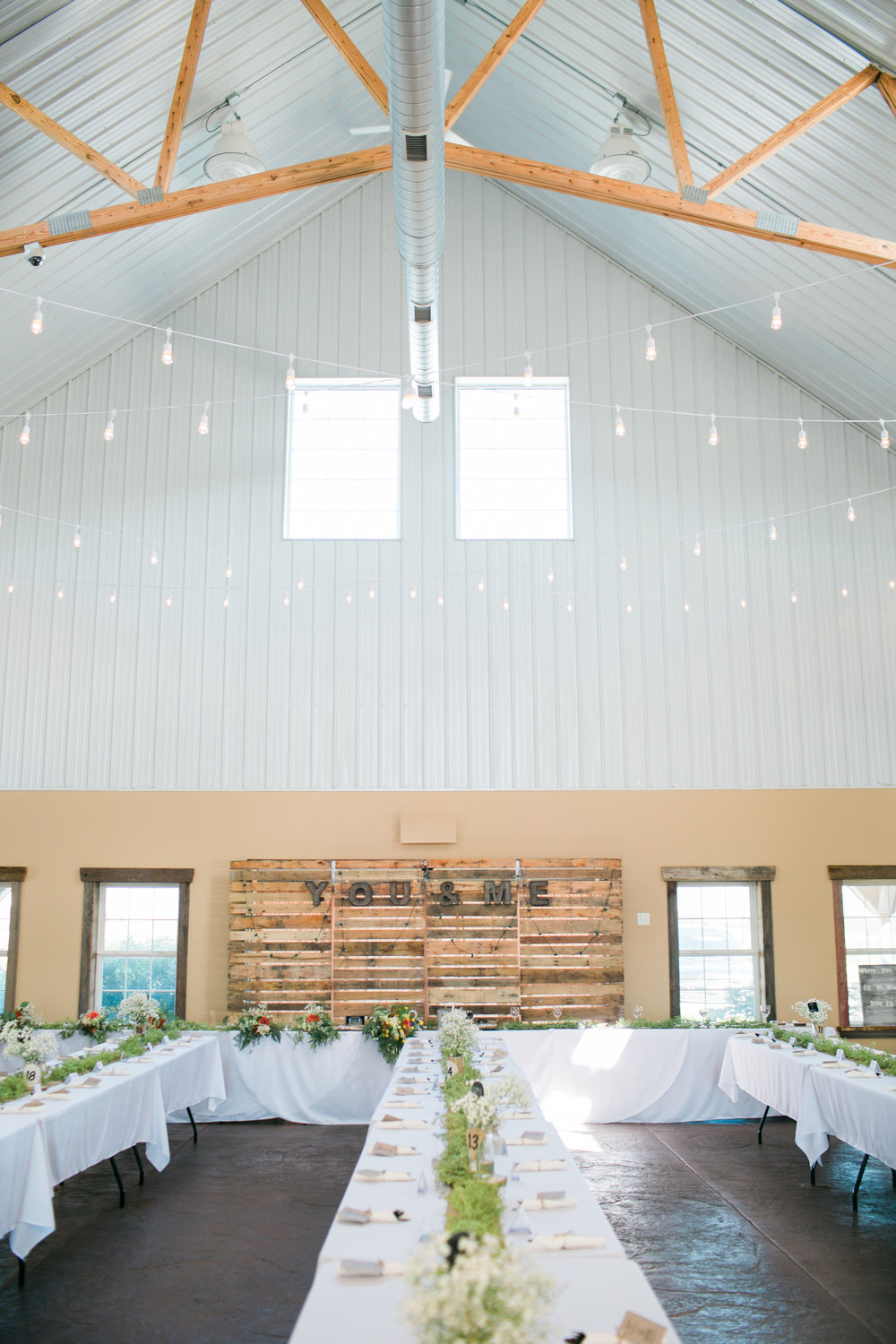 Bright and airy reception space at The Outpost Center in Chaska Minnesota with cafe lights and rustic details