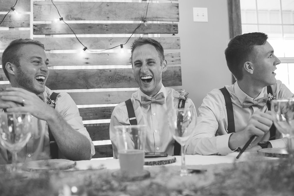 Groomsmen reactions to toasts during rustic summer wedding at The Outpost Center in Chaska Minnesota
