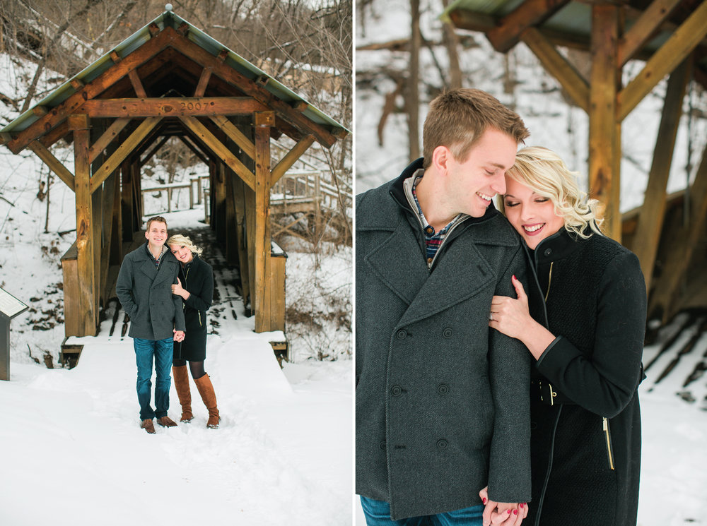 Minnesota couple for engagement photos in Taylors Falls in front of bridge and cuddling in winter coats