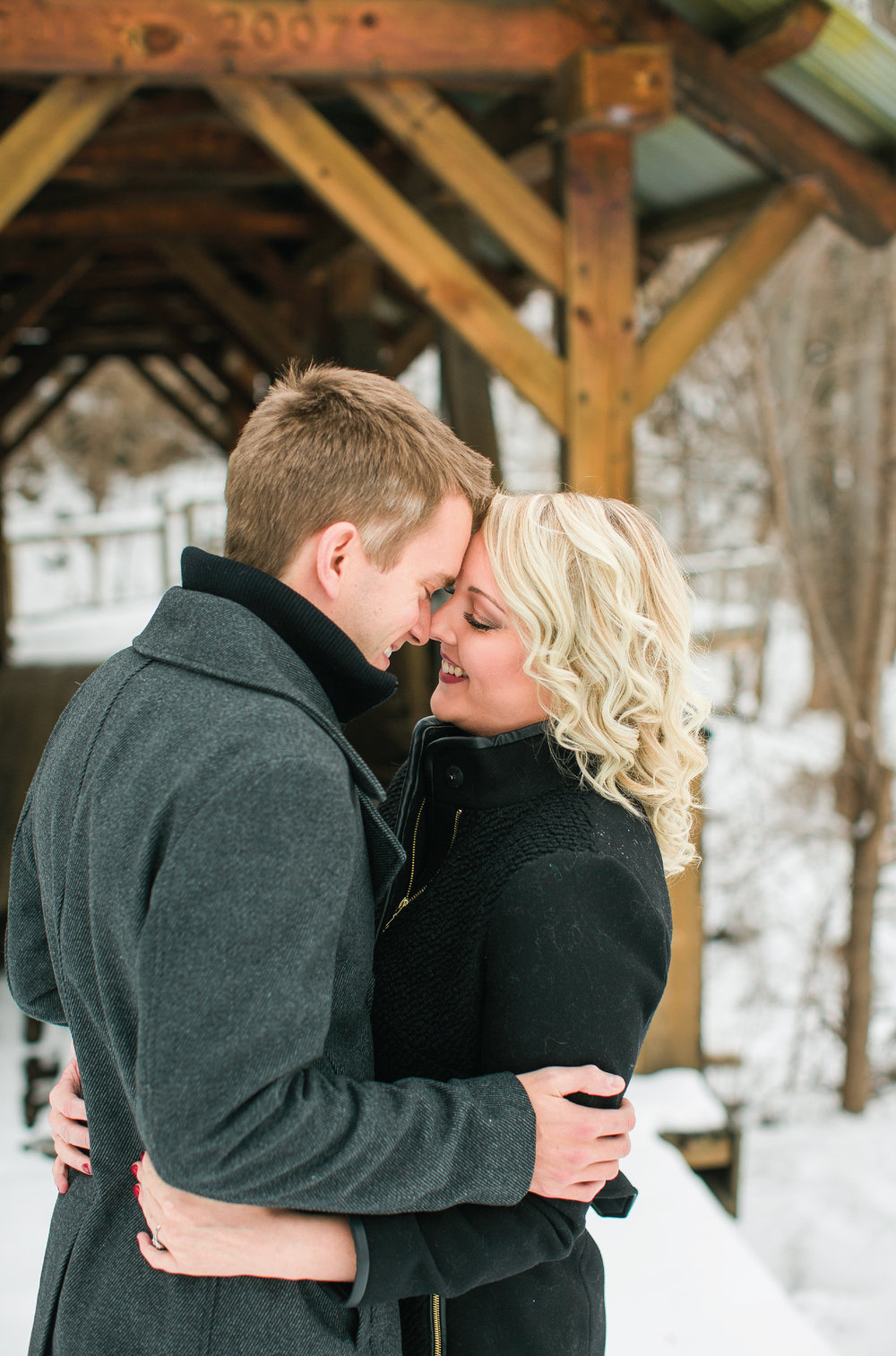 Minnesota engagement photos in Taylors Falls couple snuggling for kiss in winter coats