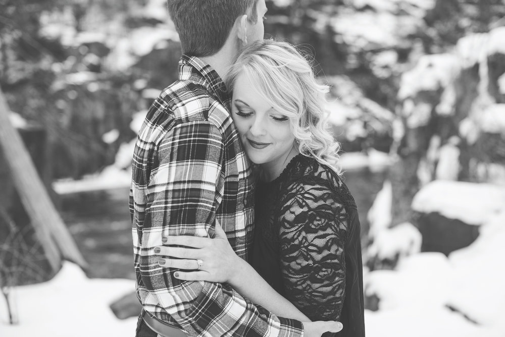 Minnesota snowy winter engagement photos in Taylors Falls Minnesota hugging in black and white
