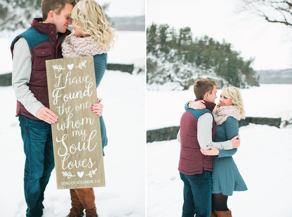 Taylors Falls Minnesota winter snowy engagement session couple holding love sign