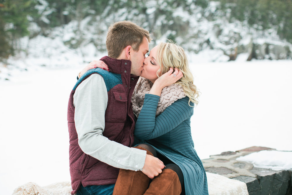 Taylors Falls Minnesota snowy winter engagement session couple sitting and kissing with woods background