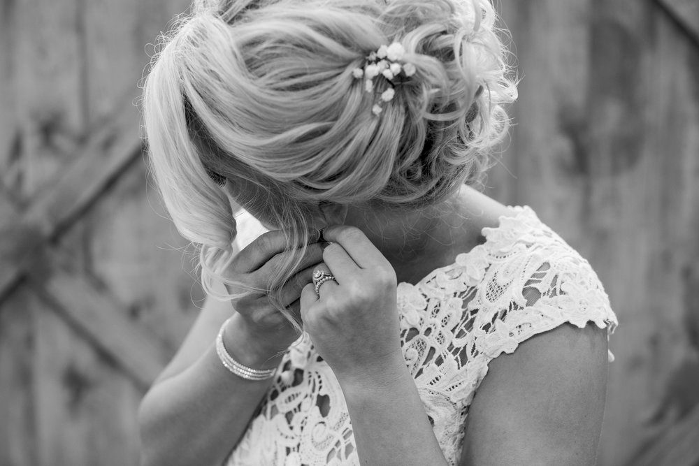 Bride getting ready putting earrings in at rustic Minnesota wedding at The Outpost Center in Chaska Minnesota