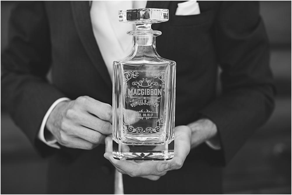 Groom reading letter from bride on wedding day during summer Minnesota wedding opens custom liquor bottle