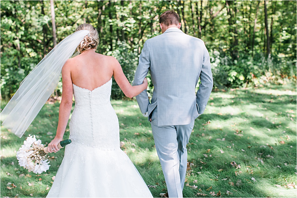 Bride and groom walking outside at Minnesota summer wedding in Buffalo MN photographed by Mallory Kiesow, Minnesota wedding photographer