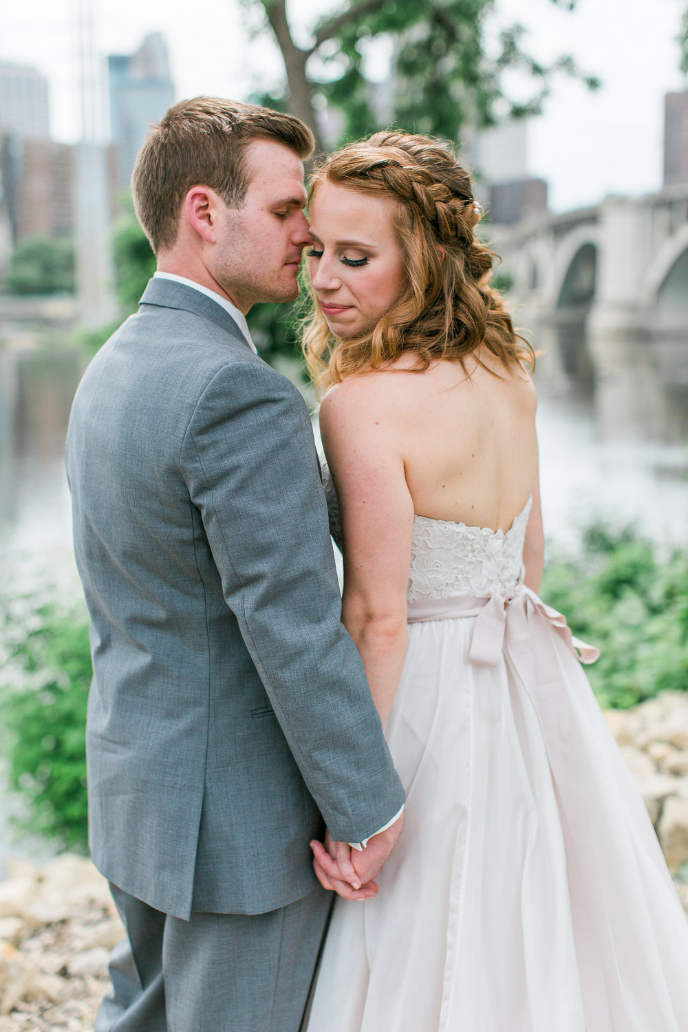 Bride and groom cuddle in front of Minneapolis skyline on St. Anthony Main during summer wedding at Minneapolis Event Centers