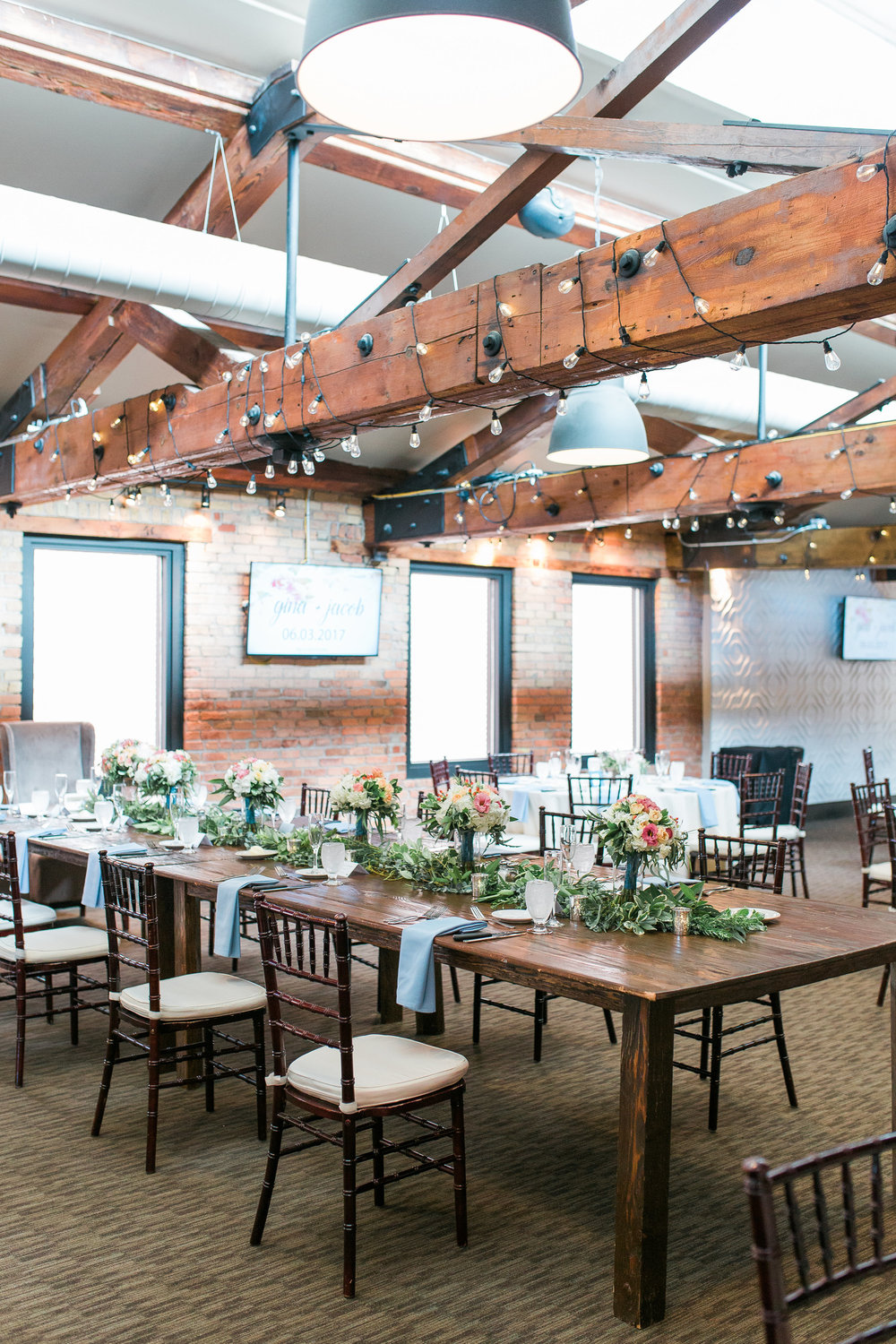 Rustic tablescape with wood beams and cafe lights at Minneapolis Event Centers wedding with floral head table centerpiece
