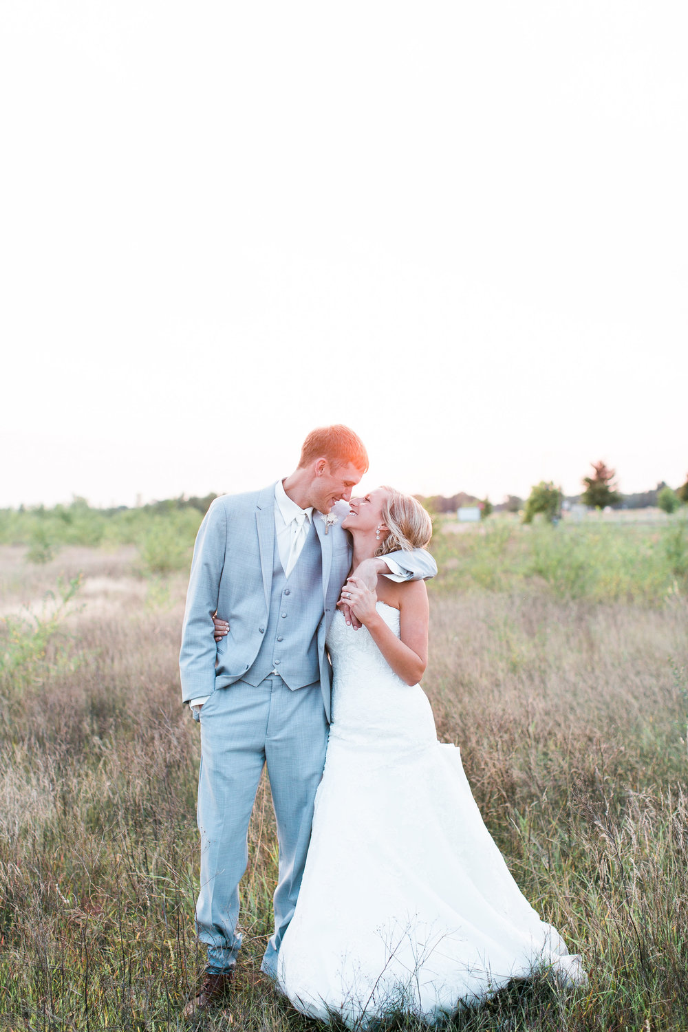 Bride and groom kissing in a field at sunset in rural Minnesota wedding