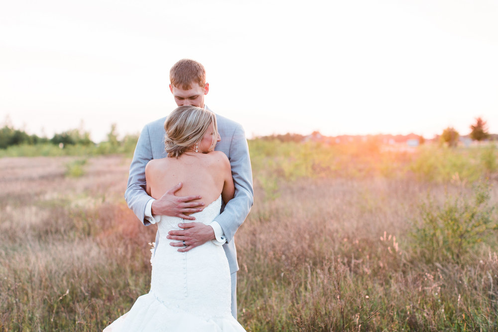 Bride and groom embracing in field at rural Minnesota wedding at sunset