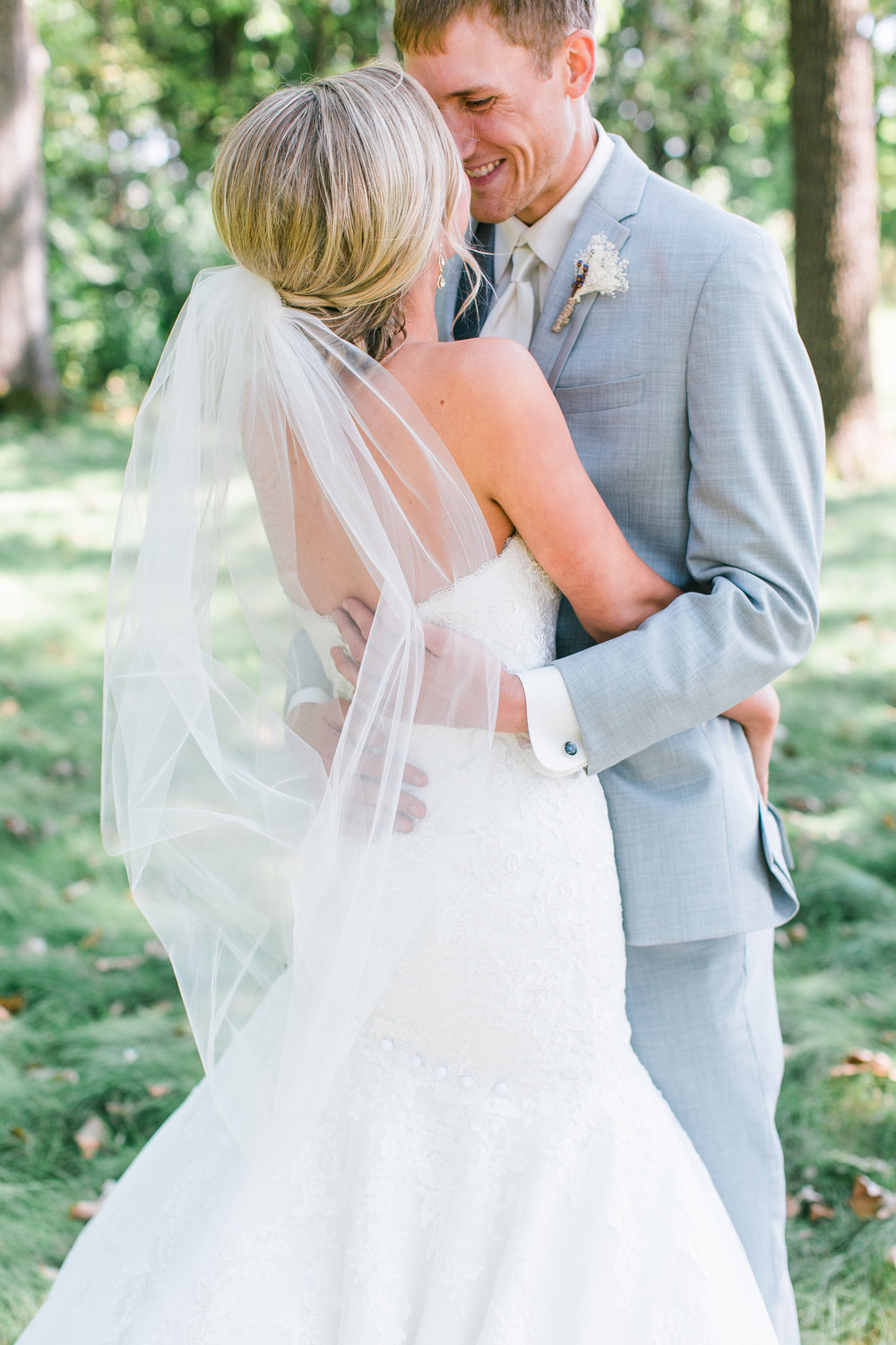 Minnesota bride and groom embracing on wedding day grey suit with veil Buffalo wedding Minnesota wedding photography Mallory Kiesow Photography