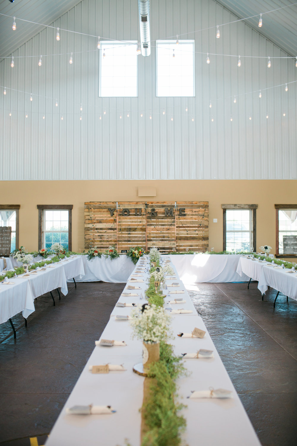 The Outpost Center in Chaska Minnesota reception space setup white cafe lights rustic Minnesota wedding photography Mallory Kiesow Photography