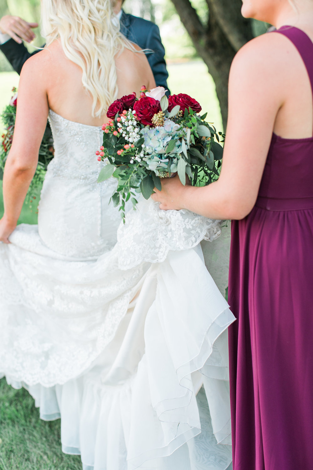 Minnesota burgundy wedding bridesmaid holding bride's dress Minnesota wedding photography Mallory Kiesow Photography