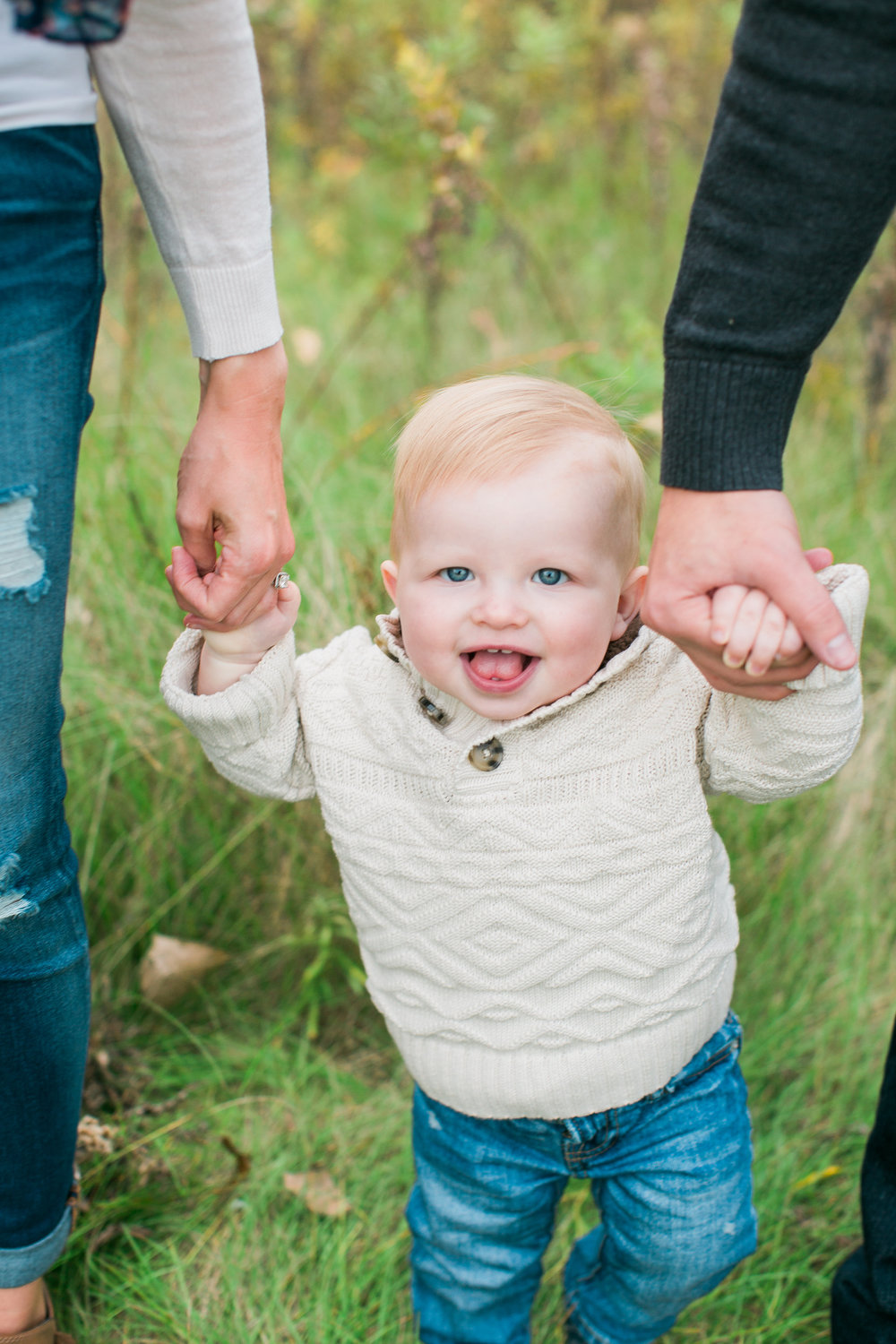 Toddler one year old holding mom and dads hands in rustic field in Minnesota fall family session Minnesota family photographer Mallory Kiesow Photography