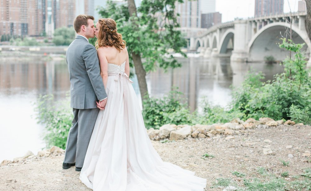 Bride and groom kissing in front of stone arch bridge in Minneapolis St Anthony Main Minneapolis Event Center wedding Minnesota wedding photography Mallory Kiesow photography