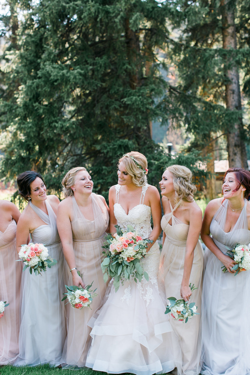 Boho bride with bridesmaids in neutral dresses with bouquets laughing Montana Big Sky Lone Mountain Ranch wedding Minnesota wedding photography Mallory Kiesow Photography