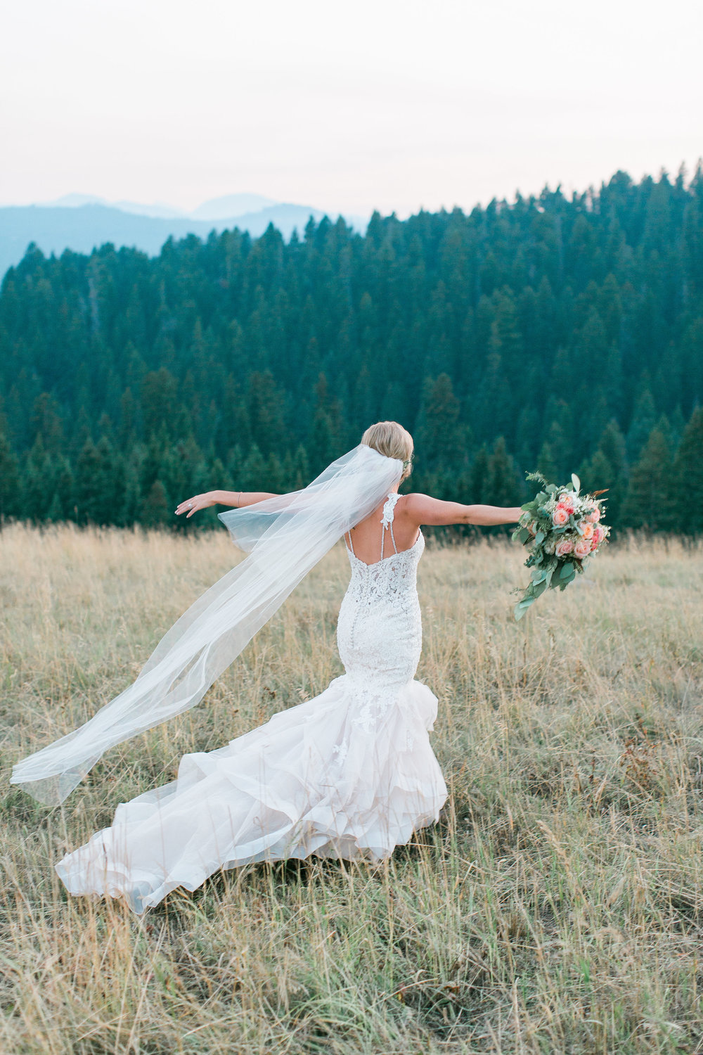 Boho bride walking with arms out free spirit and mountains in background Big Sky Montana Lone Mountain Ranch wedding Minnesota wedding photography Mallory Kiesow Photography