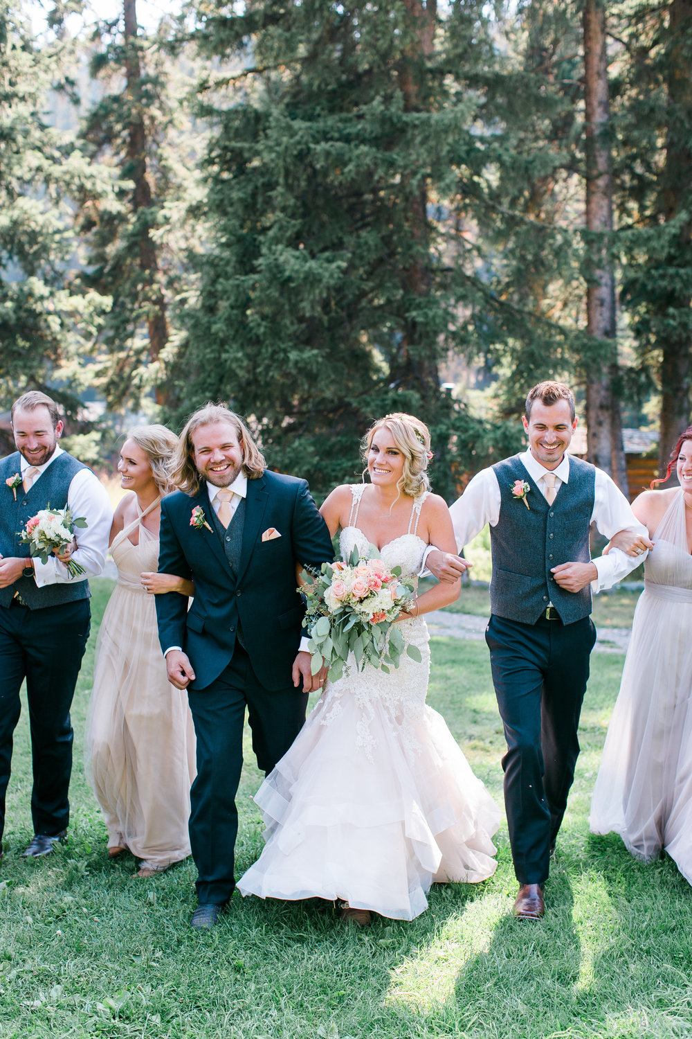 Wedding party with black suits and neutral bridesmaid dresses walking and laughing Big Sky Montana Lone Mountain Ranch wedding Minnesota wedding photography Mallory Kiesow Photography