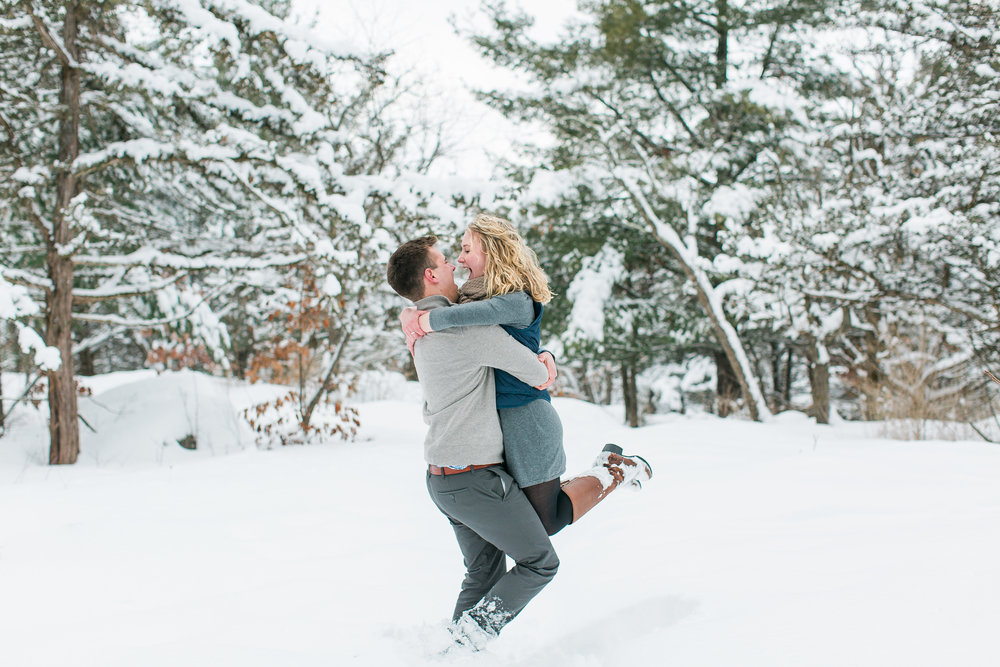 Engaged couple playing and laughing in snow in Taylors Falls engagement session Minnesota engagement photography Mallory Kiesow Photography