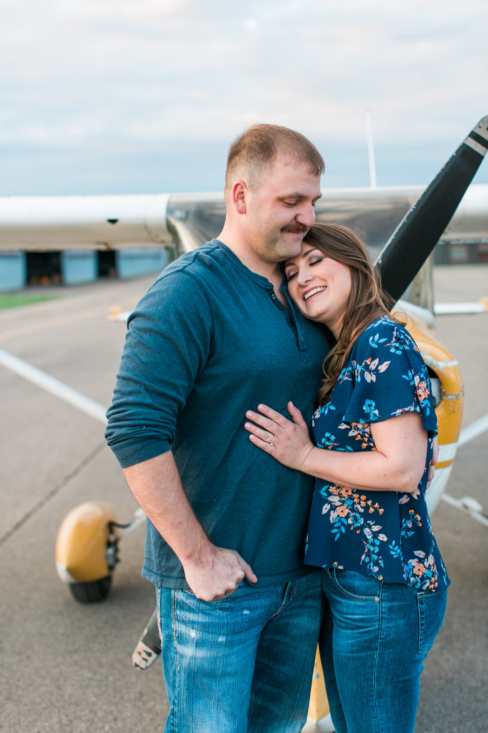 Engaged couple embracing in front of airplane at Flying Cloud Airport in Eden Prairie Minnesota Minnesota engagement photographer Mallory Kiesow Photography