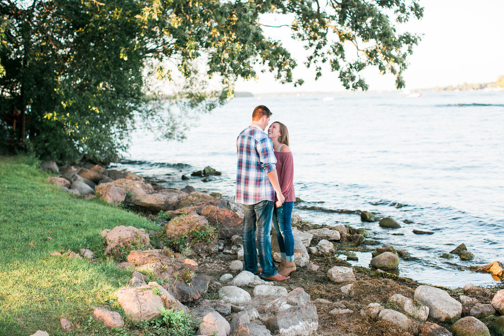 Engaged couple holding hands on Lake Minnetonka in Excelsior Minnesota for engagement photos Minnesota engagement photographer Mallory Kiesow Photography