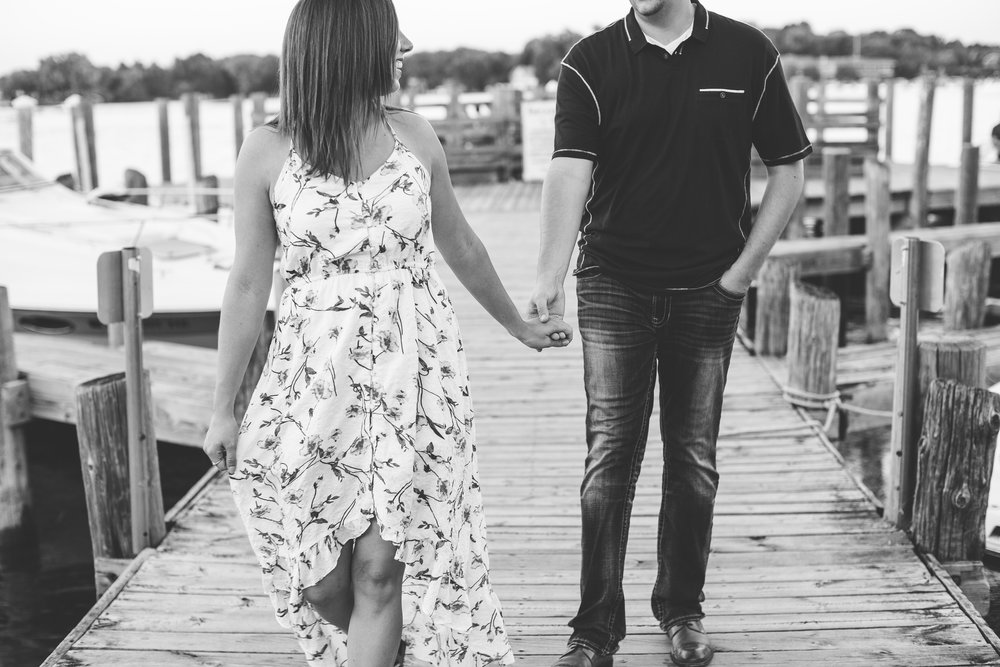 Engaged couple walking and holding hands in black and white photo on Lake Minnetonka dock in Excelsior Minnesota engagement session Minnesota engagement photographer Mallory Kiesow Photography