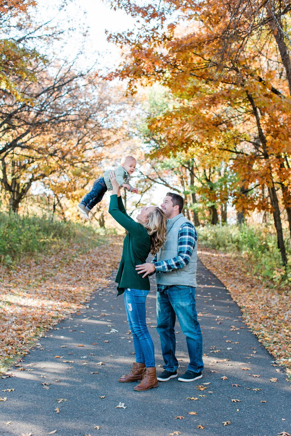 Family of mom dad and baby in Minnesota fall family session mom holding baby in air Minnesota family photographer Mallory Kiesow Photography