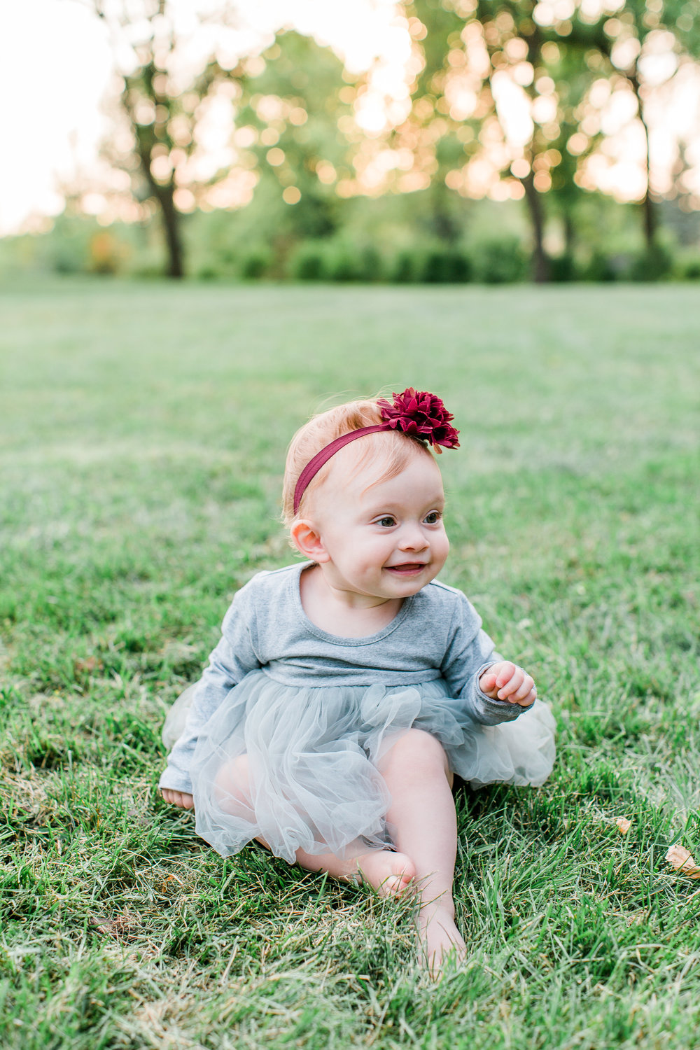 One year old girl in gray tutu dress and burgundy bow in the grass Minnesota family photographer Mallory Kiesow Photography