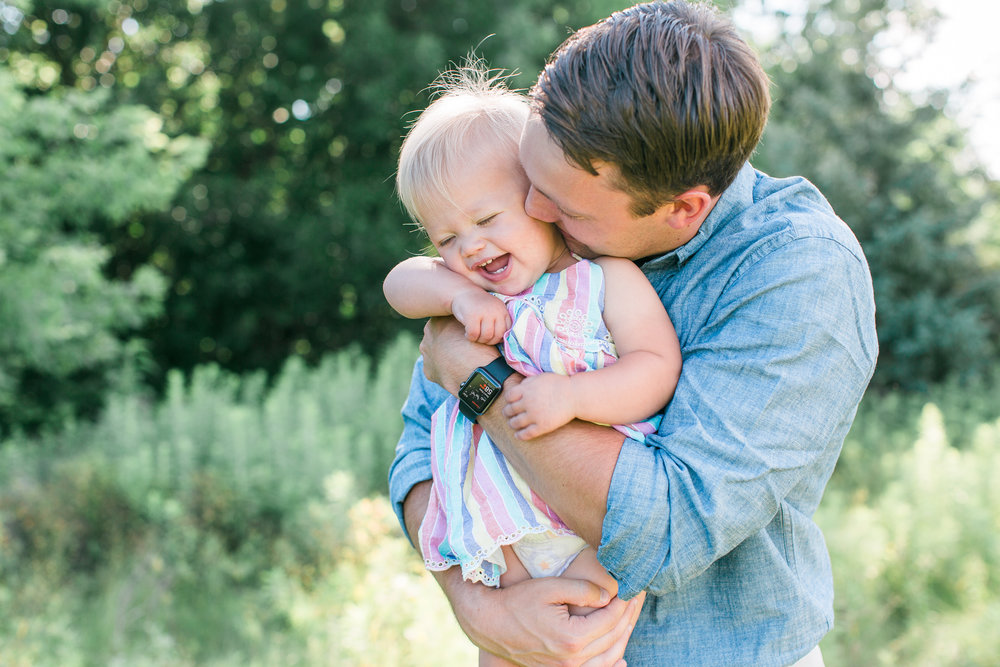 Dad cuddling and making baby laugh in rural field in Minnesota for family photos Minnesota family photographer Mallory Kiesow Photography