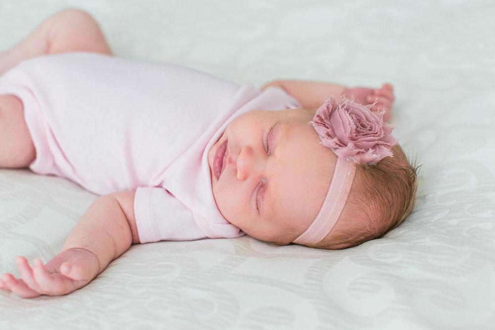 Newborn baby girl sleeping on bed in-home lifestyle newborn session Minnesota newborn photographer Mallory Kiesow Photography