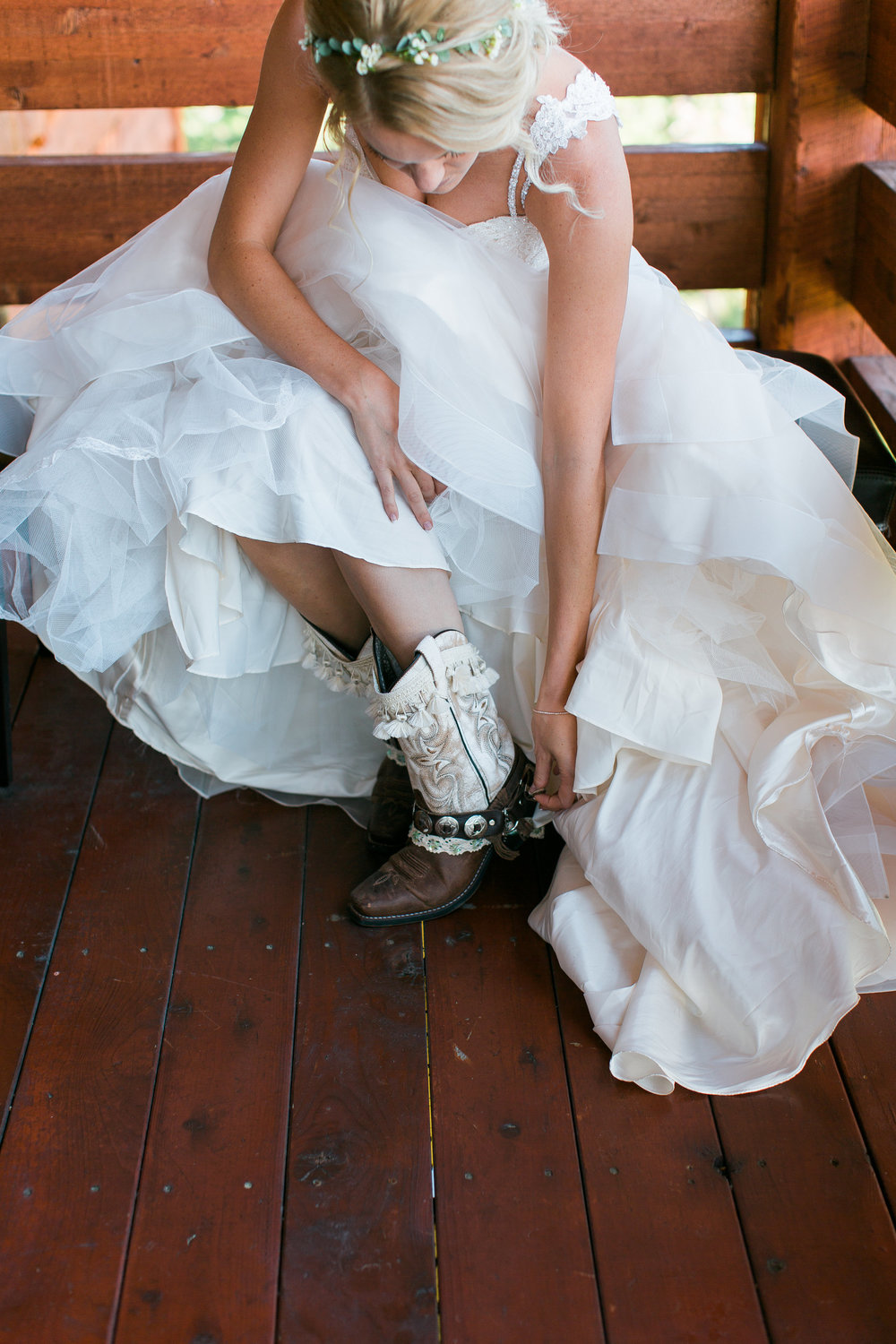 Boho bride putting on cowboy boots Montana Lone Mountain Ranch wedding Minnesota wedding photography Mallory Kiesow Photography