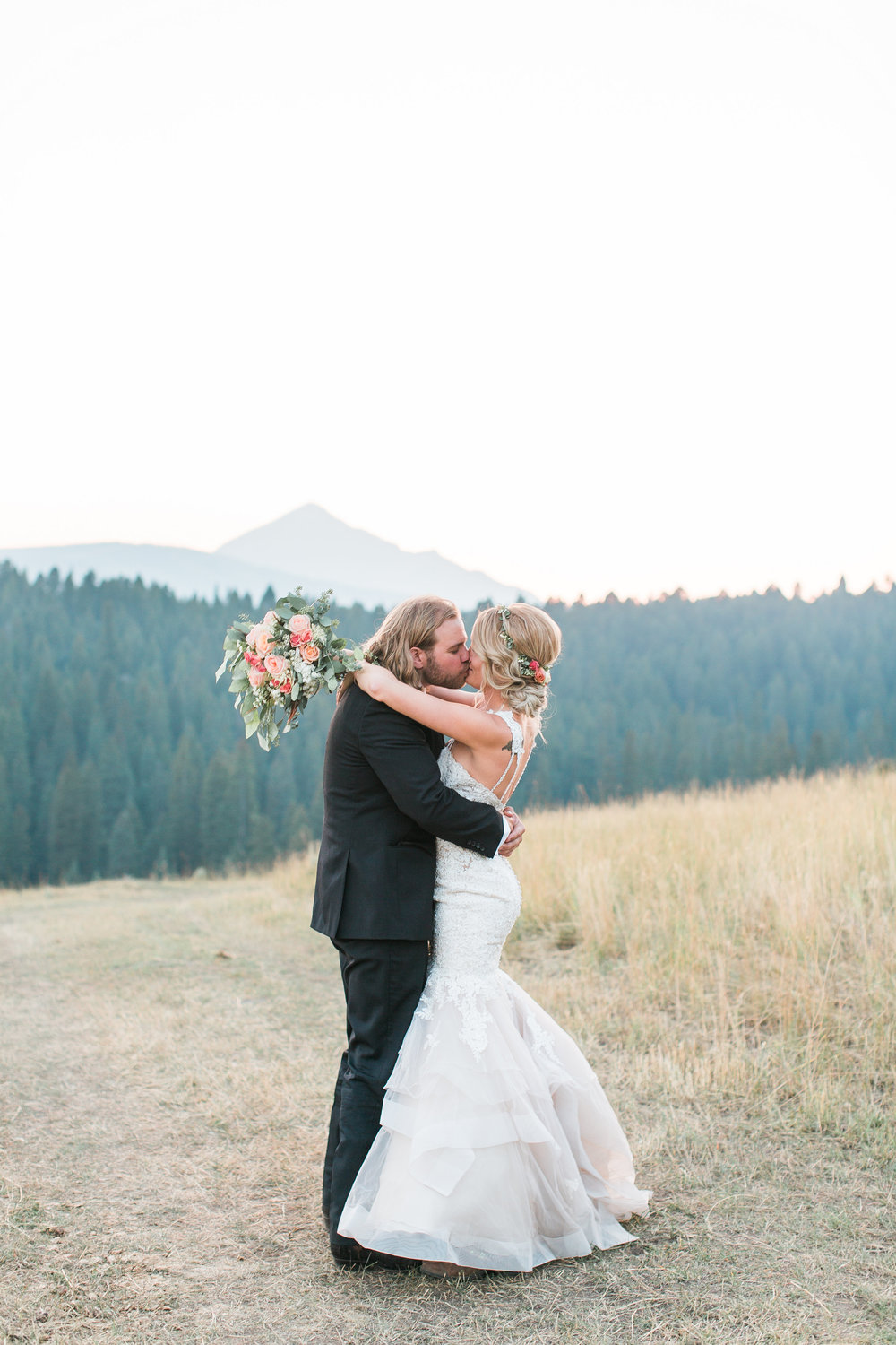 Boho bride and groom kissing with mountains in the background in Big Sky Montana Lone Mountain Ranch wedding Minnesota wedding photography Mallory Kiesow Photography