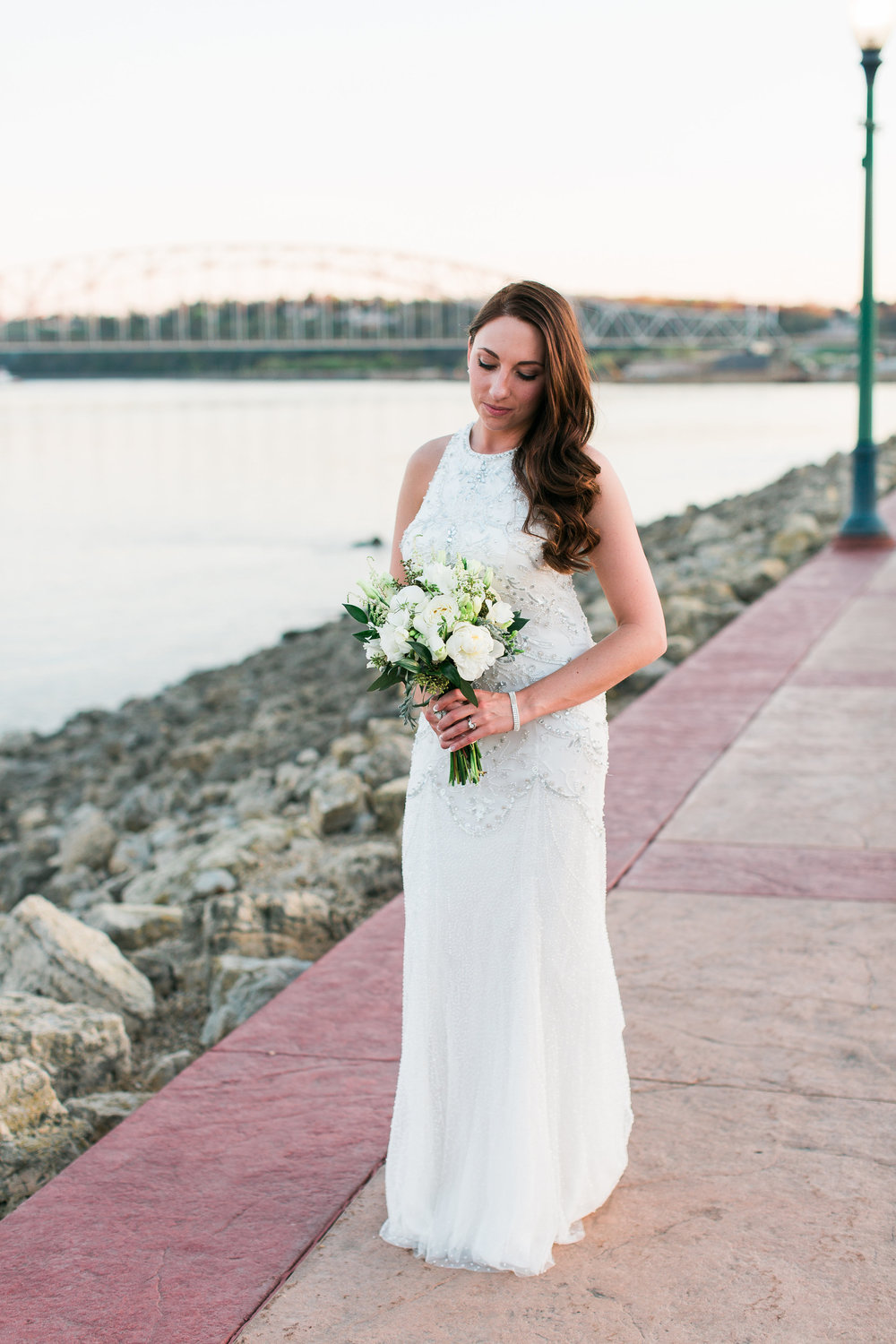 Bridal portrait of bride with beaded dress hair down along riverside in Dubuque Iowa wedding Minnesota wedding photography Mallory Kiesow Photography