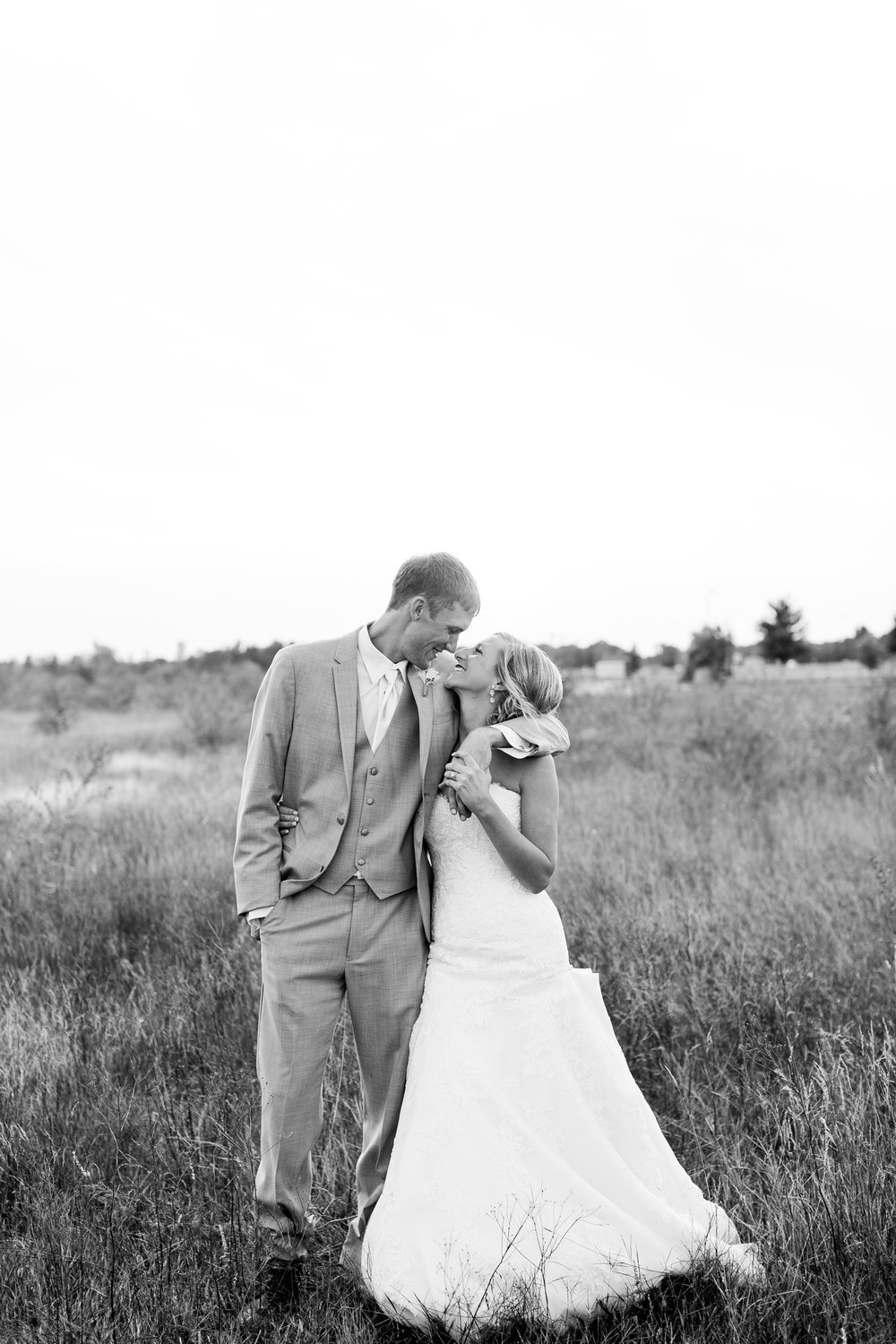 Bride and groom kissing in field in black and white Buffalo Minnesota wedding Minnesota wedding photography Mallory Kiesow Photography