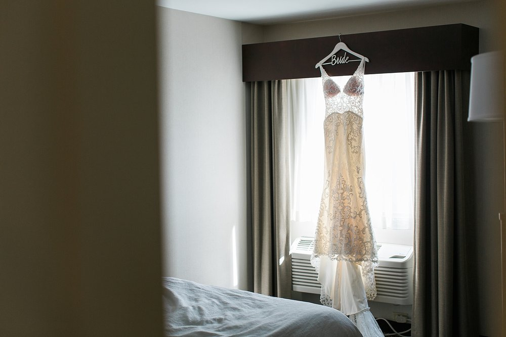 Wedding dress in hotel room window for wedding at the Chart House Summer Wedding Lakeville Minnesota Minneapolis Wedding Photographer Mallory Kiesow