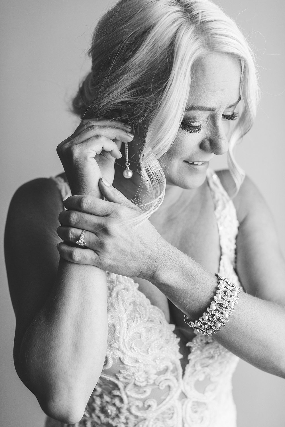 Bride putting on earrings for wedding at the Chart House Summer Wedding Lakeville Minnesota Minneapolis Wedding Photographer Mallory Kiesow