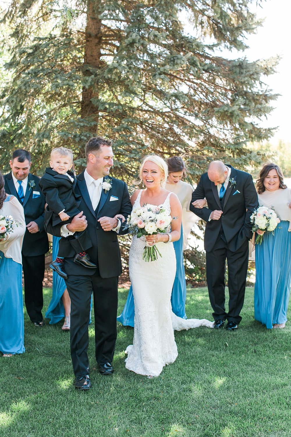 Wedding party black suits blue dresses walking and laughing on wedding day at the Chart House Summer Wedding Lakeville Minnesota Minneapolis Wedding Photographer Mallory Kiesow