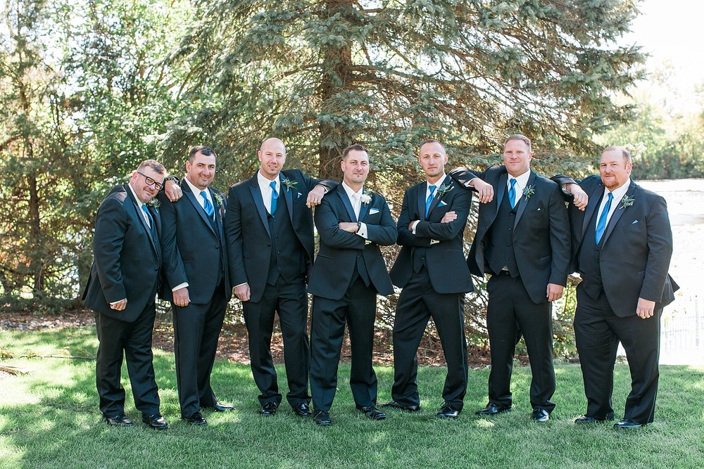 Groom and groomsmen in black suits suits on wedding day at the Chart House Summer Wedding Lakeville Minnesota Minneapolis Wedding Photographer Mallory Kiesow