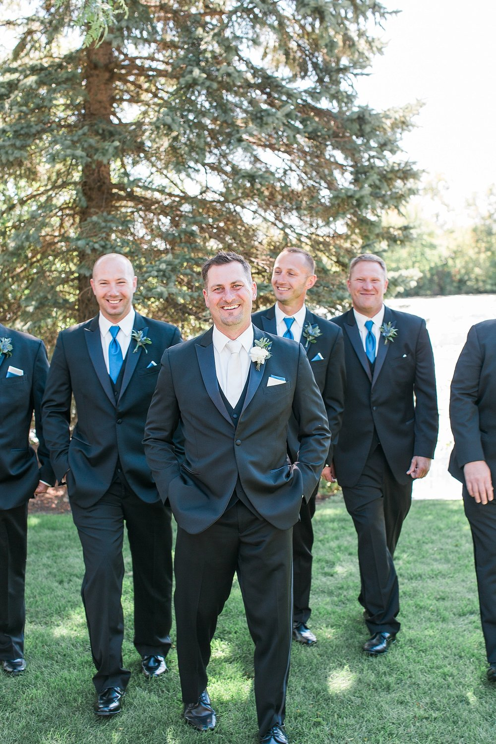 Groom and groomsmen in black suits suits walking and laughing on wedding day at the Chart House Summer Wedding Lakeville Minnesota Minneapolis Wedding Photographer Mallory Kiesow