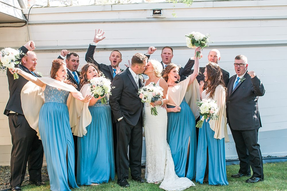 Wedding party cheering in black suits suits and blue dresses on wedding day at the Chart House Summer Wedding Lakeville Minnesota Minneapolis Wedding Photographer Mallory Kiesow