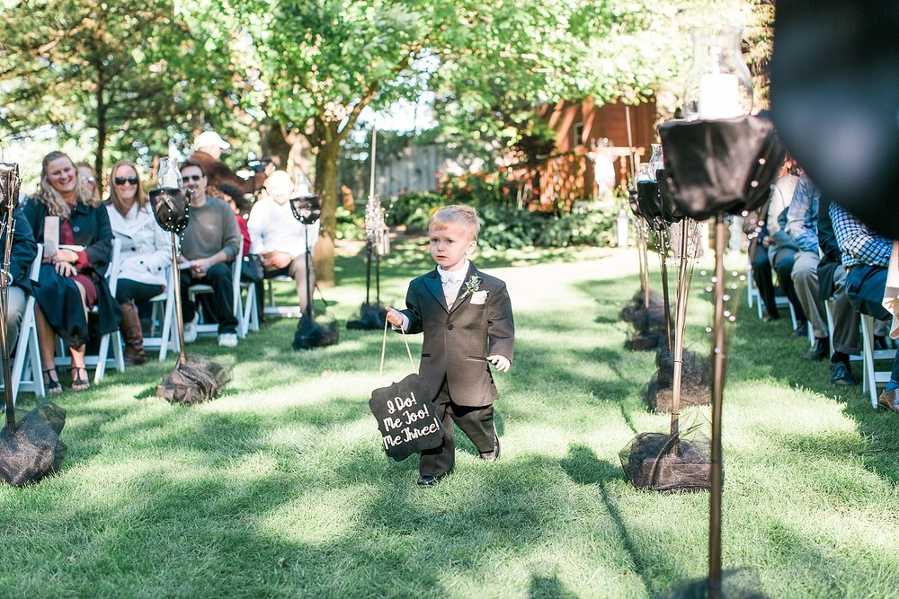 Outdoor wedding ceremony ring bearer walking down aisle at the Chart House Summer Wedding Lakeville Minnesota Minneapolis Wedding Photographer Mallory Kiesow