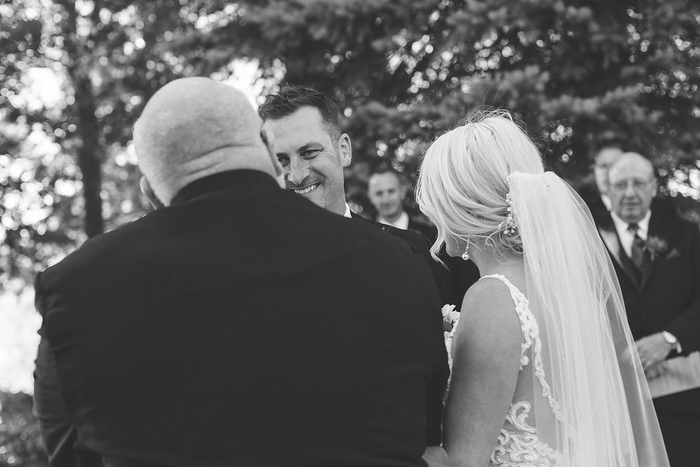 Outdoor wedding ceremony groom reaction to father giving away bride at the Chart House Summer Wedding Lakeville Minnesota Minneapolis Wedding Photographer Mallory Kiesow