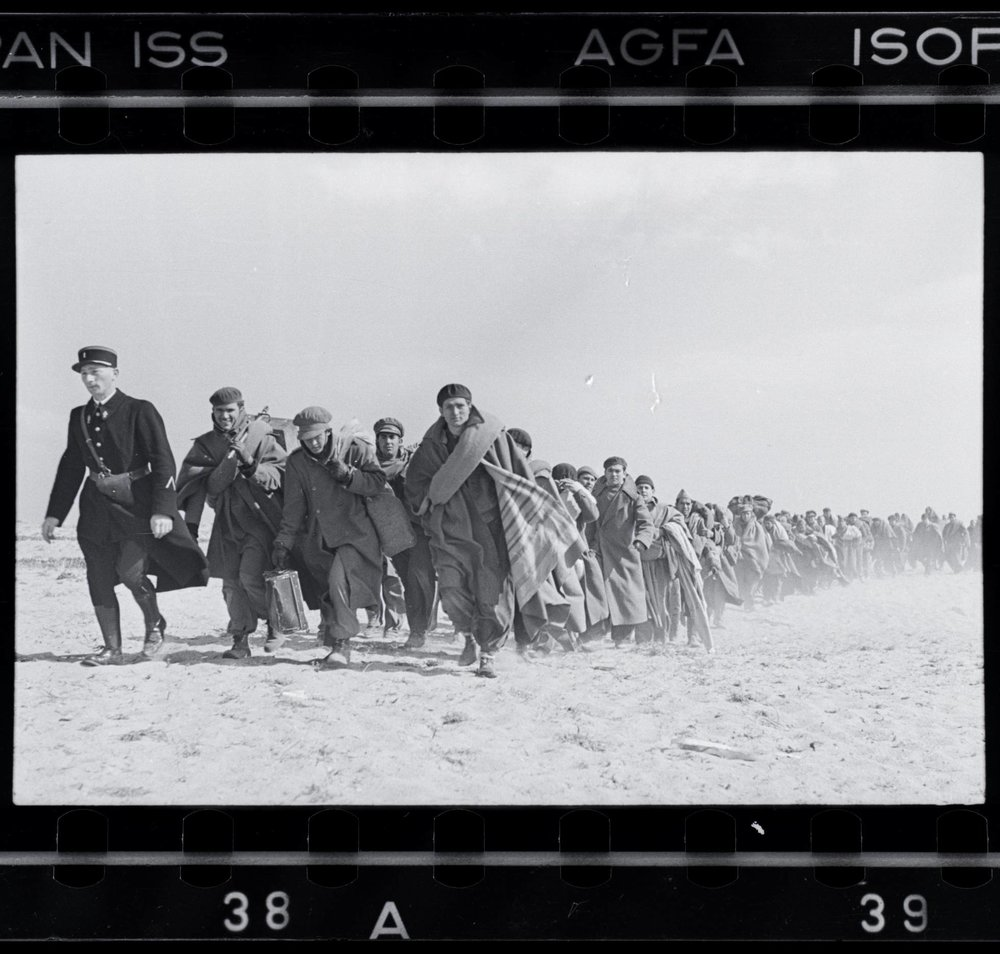 Robert Capa, Refugees walking on the beach, in the French internment camp for Republican exiles, Le Barcarès, France, March 1939.  Image credit: International Center for Photography / Magnum, via Wikimedia Commons.