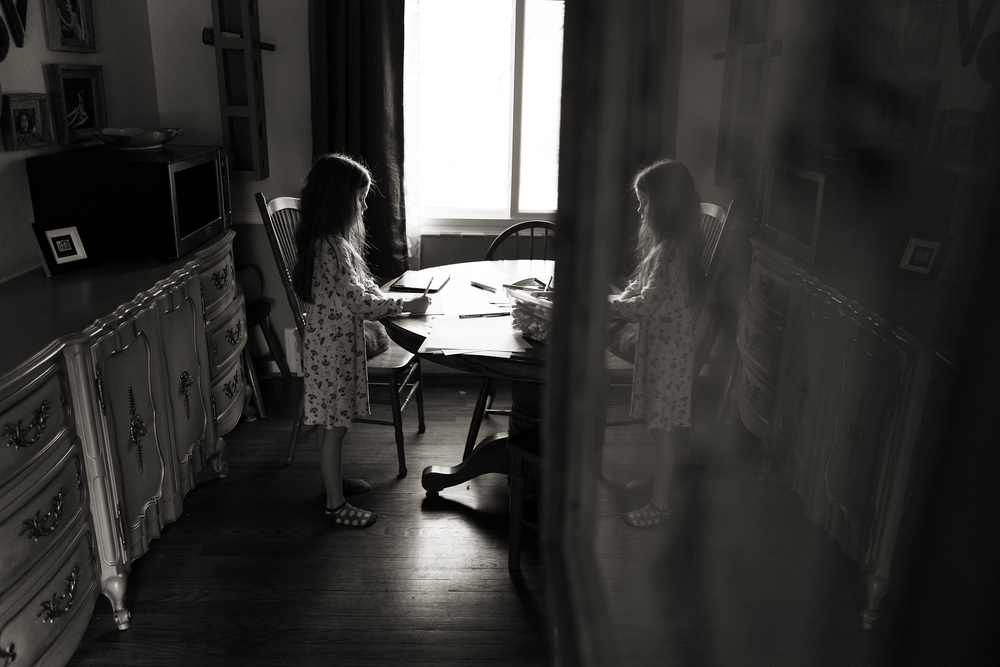 Columbus photographer captured 6 year old daughter drawing in Worthington home. Reflection with vintage furniture.