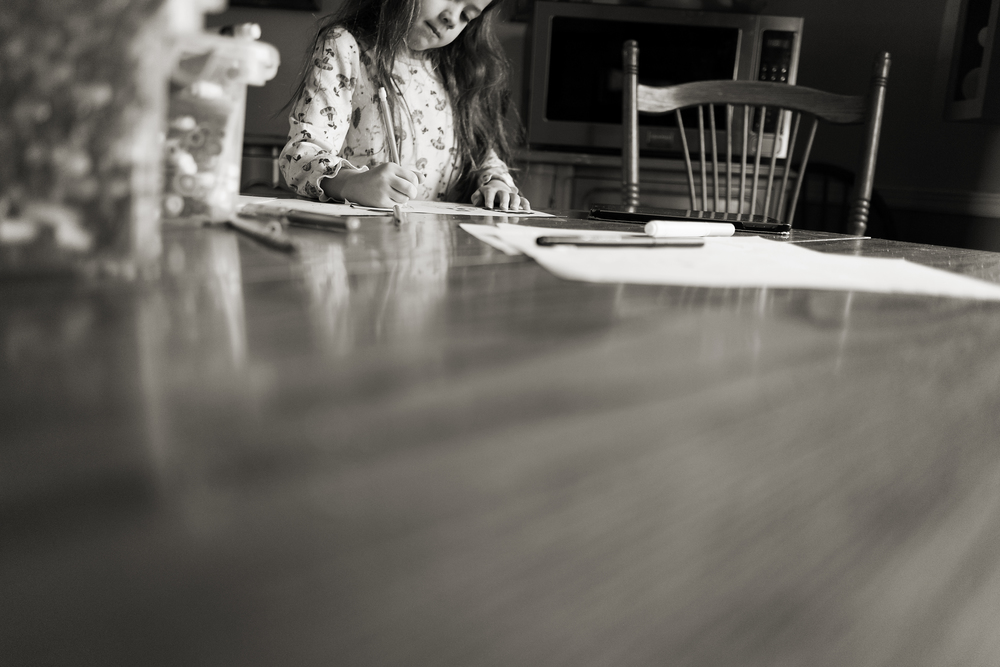 Columbus photographer captures 6 year old daughter coloring at vintage kitchen table in Worthington home.
