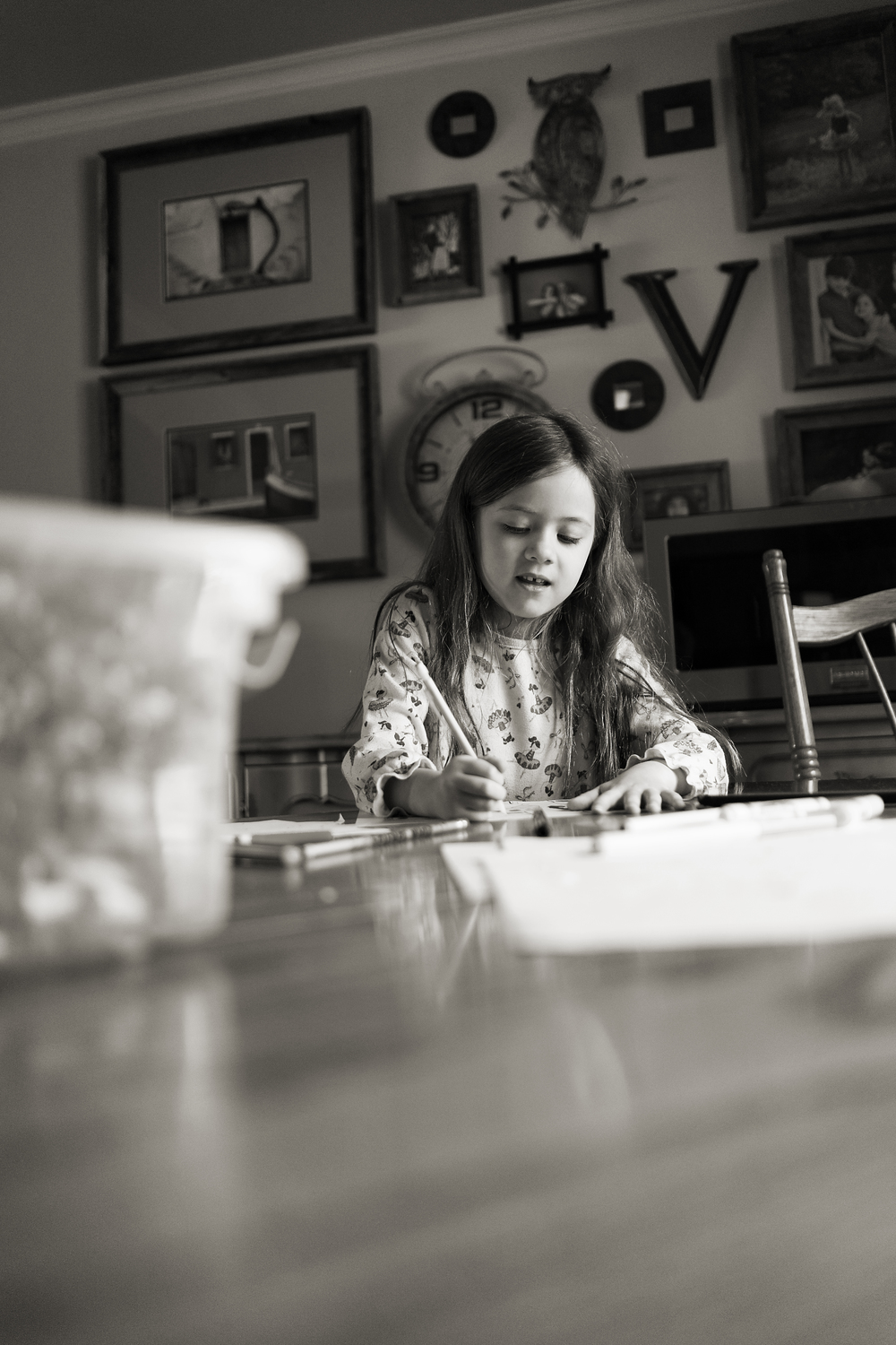 Columbus photographer takes lifestyle portraits of six year old daughter in vintage worthington home surrounded by art gallery walls.