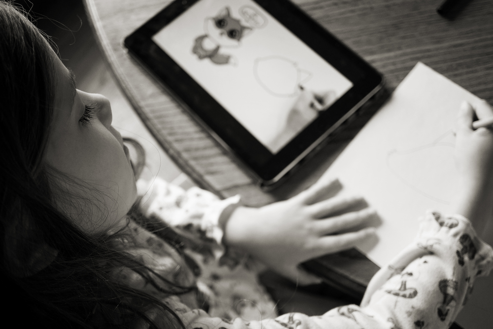 Columbus photographer photographs daughter following ipad drawing instructions in Worthington home.