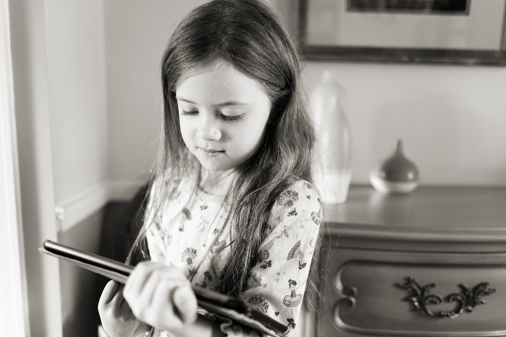 Child with long hair in pajamas with ipad in old home in Worthington, Oh.